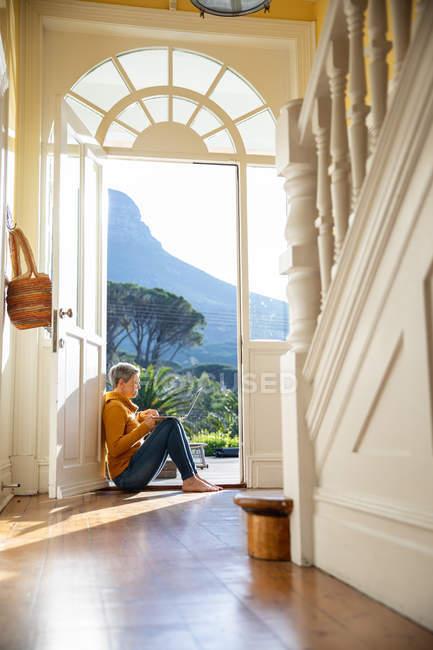 Seitenansicht einer reifen kaukasischen Frau, die auf dem Fußboden in der Eingangstür ihres Hauses in der Sonne sitzt und einen Laptop benutzt, mit sonnenbeschienenen Bäumen im Hintergrund, vom Flur ihres Hauses aus gesehen — Stockfoto