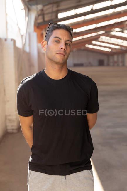 Vista frontal de perto de um jovem vestindo uma camiseta preta e óculos de sol na cabeça, olhando para a câmera com as mãos atrás das costas, de pé em um armazém abandonado — Fotografia de Stock
