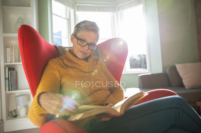 Вид спереду крупним планом зрілої кавказької жінки з коротким сивим волоссям в окулярах сидять у червоному кріслі в її вітальні читанні книги, з підсвічуванням сонячного світла з вікна — стокове фото