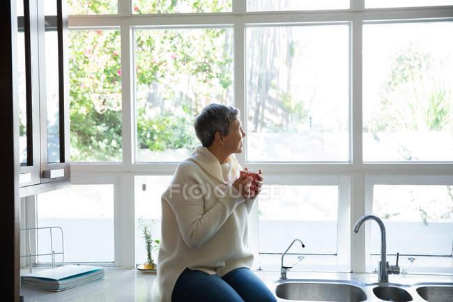 Вид збоку зрілої кавказької жінки з коротким сивим волоссям сидить на прилавку в кухні, що тримає чашку кави і дивлячись з вікна, є дерева зовні і світить сонце — стокове фото