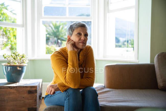 Передний вид крупным планом зрелой кавказской женщины с короткими седыми волосами, сидянана на диване в своей гостиной, с неопределенным выражением, залитым солнцем окном на заднем плане — стоковое фото