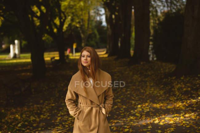 Mujer con las manos en el bolsillo caminando por el parque . - foto de stock