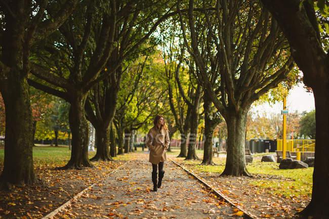 Donna con le mani in tasca passeggiando nel parco — Foto stock