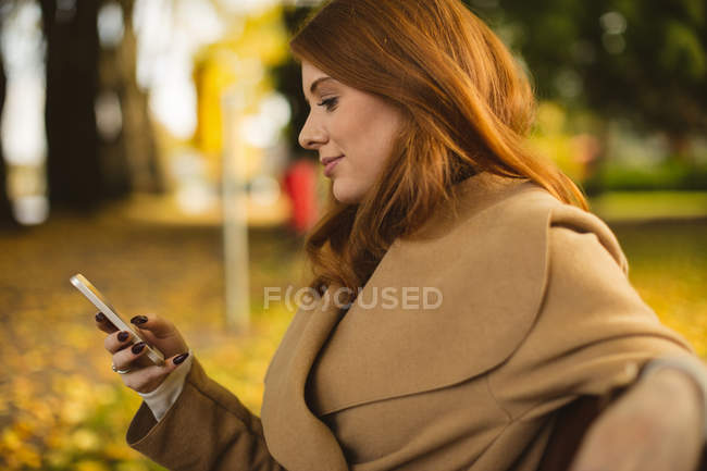 Woman using mobile phone in the park. — Stock Photo
