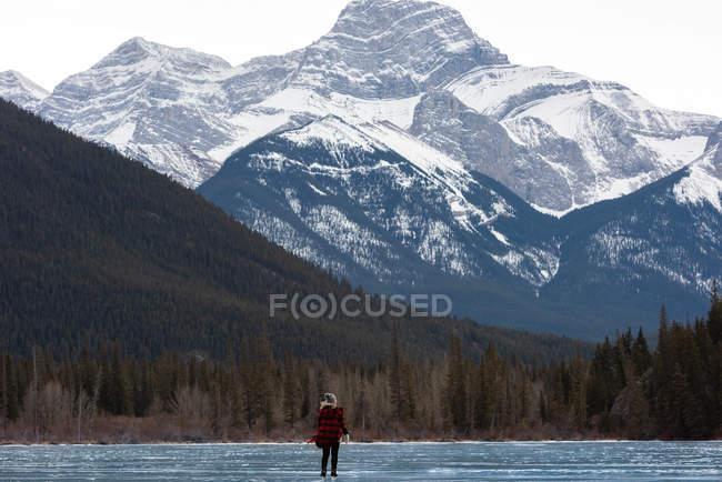 Vue arrière de la femme blonde debout sur une patinoire naturelle contre la montagne en arrière-plan — Photo de stock