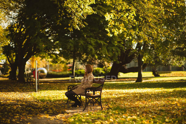 Woman sitting on a bench in the park. — Stock Photo
