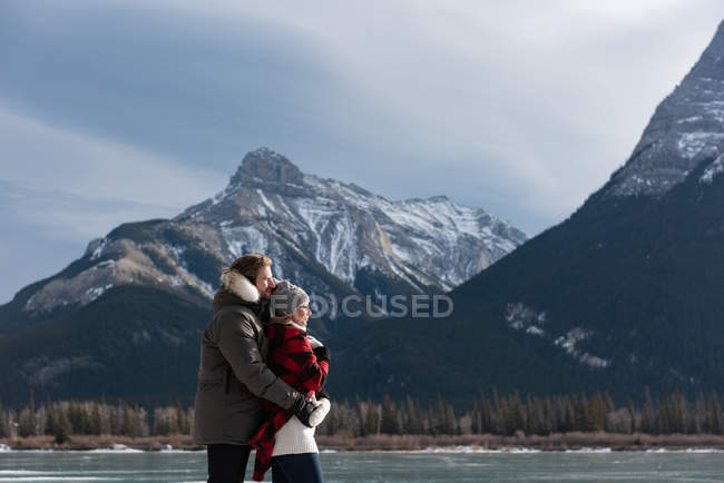 Seitenansicht eines jungen kaukasischen Paares, das mit dem Arm im Hintergrund in einer natürlichen Schneelandschaft steht — Stockfoto