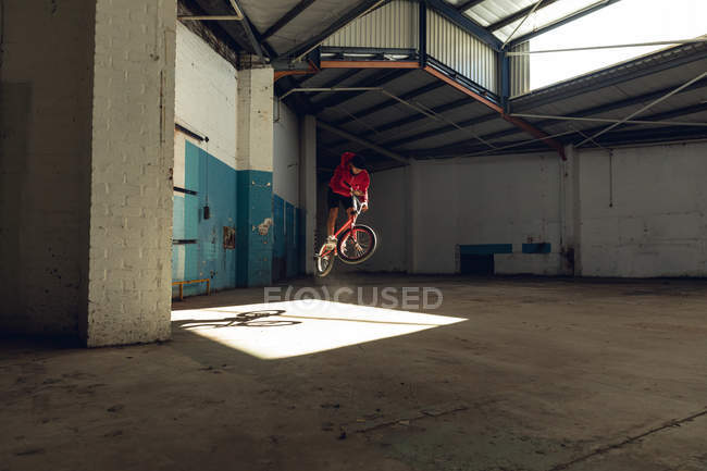 Side view of a young Caucasian man doing a jump on a BMX bike and turning the handlebars in an abandoned warehouse — Stock Photo