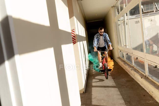 Vista frontal de un joven caucásico con gafas de sol montando una bicicleta Bmx con granadas de humo verde y naranja unidas a ella en un estrecho pasillo en un almacén abandonado al sol - foto de stock