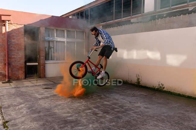 Vista lateral de un joven caucásico con gafas de sol saltando sobre granadas de humo verde y naranja de pie en una bicicleta Bmx fuera de un almacén abandonado bajo el sol - foto de stock