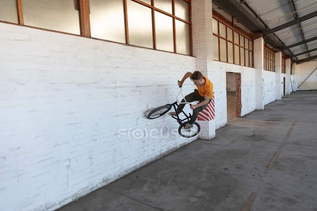 Vue de face d'un jeune homme caucasien sur un vélo BMX dans un entrepôt abandonné — Photo de stock