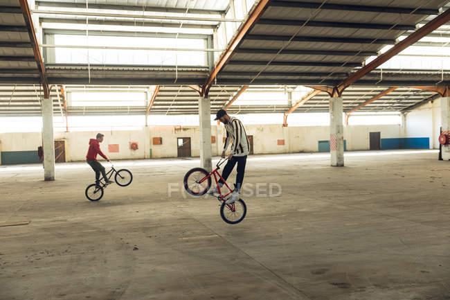 Vista lateral de dos jóvenes caucásicos que se enfrentan a direcciones opuestas balanceándose en las ruedas traseras de sus bicicletas Bmx mientras practican trucos en un almacén abandonado, el piloto en primer plano está saltando del suelo - foto de stock