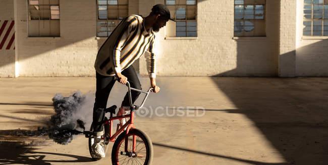 Vista frontal de un joven caucásico montando una bicicleta Bmx con una granada de humo gris unida a ella, en un almacén abandonado - foto de stock