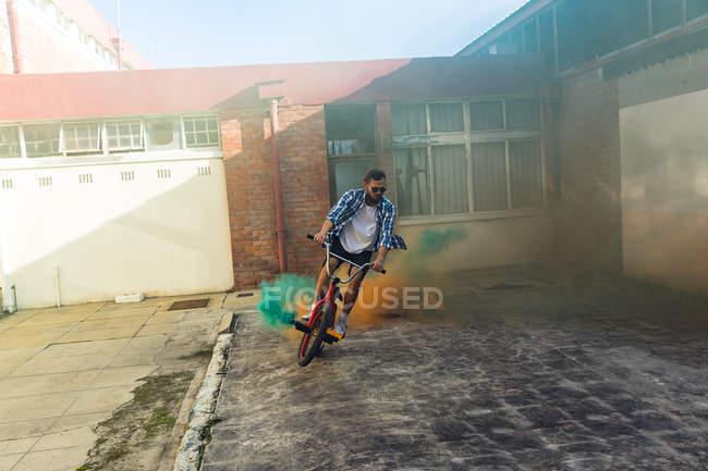 Vista frontal de un joven caucásico con gafas de sol montando una bicicleta Bmx con granadas de humo verde y naranja unidas a ella fuera de un almacén abandonado bajo el sol - foto de stock