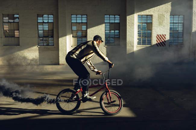 Vista lateral de un joven caucásico montando una bicicleta Bmx con una granada de humo gris unida a ella, en un almacén abandonado - foto de stock