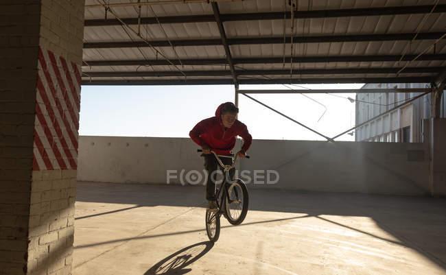 Vista frontal de un joven caucásico montando una bicicleta Bmx y balanceándose en la rueda trasera mientras practica trucos en un almacén abandonado - foto de stock