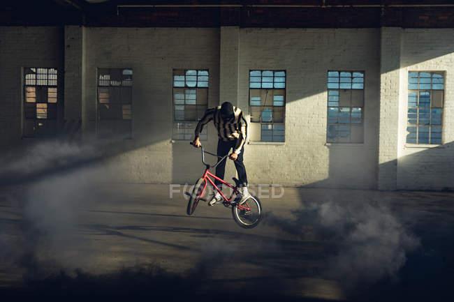 Vista lateral de un joven caucásico saltando en una bicicleta Bmx con una granada de humo gris unida a ella, en un almacén abandonado - foto de stock