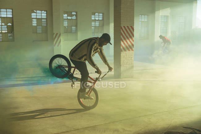 Vista lateral de dos jóvenes caucásicos montando y haciendo trucos en bicicletas Bmx con granadas de humo amarillas y azules unidas a ellos, en un almacén abandonado - foto de stock