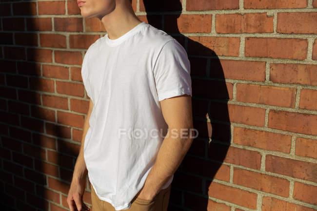 Vista lateral parte média de um jovem caucasiano vestindo uma camisa branca encostada a uma parede de tijolo ao sol — Fotografia de Stock