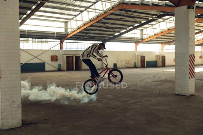Вид збоку молодого Кавказького чоловіка носіння Бейсболки їзда і стрибки на велосипеді BMX з білою димової гранати додається до нього, в покинутому складі — стокове фото