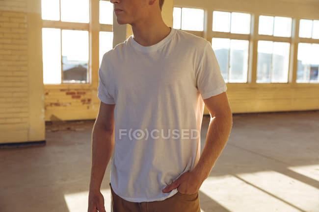 Vista frontal sección media de un joven caucásico vestido con una camiseta blanca de pie en un almacén abandonado al sol, mirando hacia otro lado, con la mano en el bolsillo - foto de stock