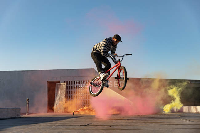 Vista lateral de un joven caucásico saltando en el aire en una bicicleta Bmx haciendo trucos en la azotea de un almacén abandonado, con granadas de humo rosa y amarilla en el fondo - foto de stock