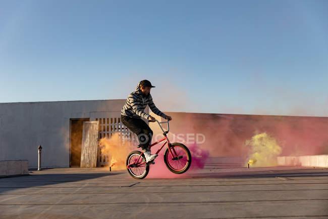 Vista lateral de un joven caucásico montando una bicicleta Bmx haciendo trucos en la azotea de un almacén abandonado, con granadas de humo naranjas, rosas y amarillas en el fondo - foto de stock