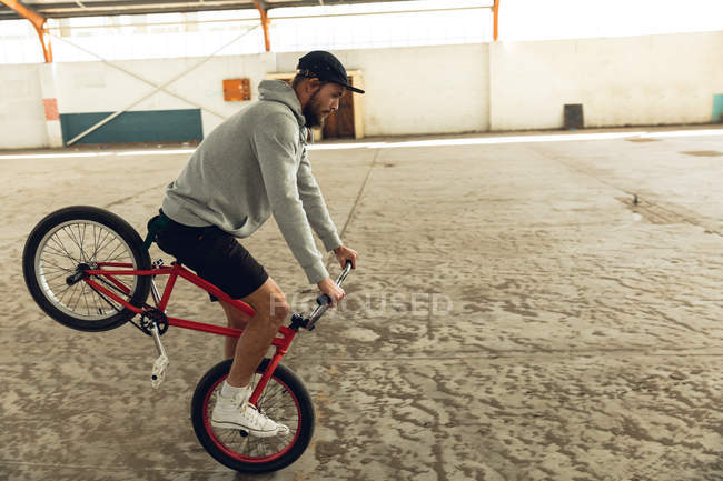 Side view close up of a young Caucasian man wearing a baseball cap, shorts and a hoodie top riding a BMX bike and balancing on the front wheel of his bike while practicing tricks in an abandoned warehouse — Stock Photo