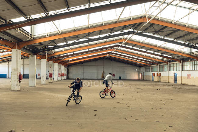 Vista frontal de dos jóvenes caucásicos mirando hacia direcciones opuestas montando bicicletas Bmx mientras practican trucos en un almacén abandonado - foto de stock