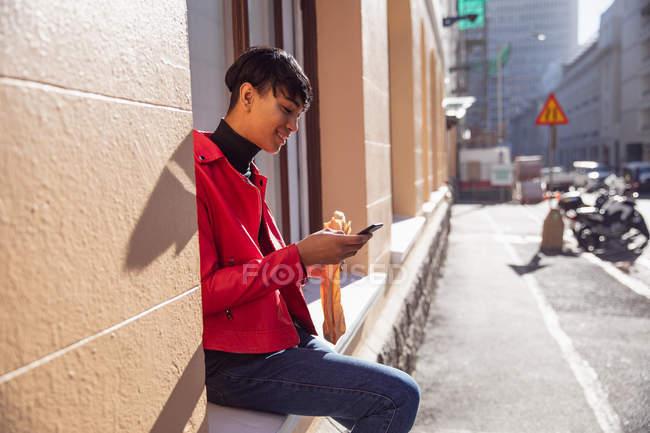 Vista lateral de un joven transexual de raza mixta de moda en la calle, usando un teléfono inteligente y comiendo un sándwich, sentado en un alféizar de la ventana - foto de stock