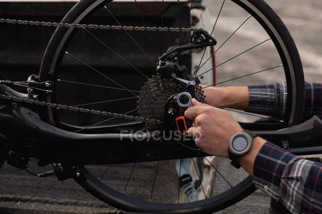 Крупним планом рук людини в інвалідному візку Монтаж лежачого велосипеда — стокове фото