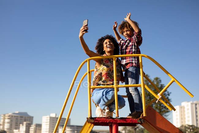Вид на молодую женщину смешанной расы и ее сына-подростка, наслаждающегося времяпрепровождением вместе, играя на детской площадке у моря, принимая селфи на горке в солнечный день — стоковое фото