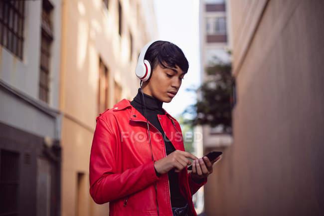Вид сбоку на модного молодого трансгендера смешанной расы на улице, используя смартфон с включенными наушниками — стоковое фото