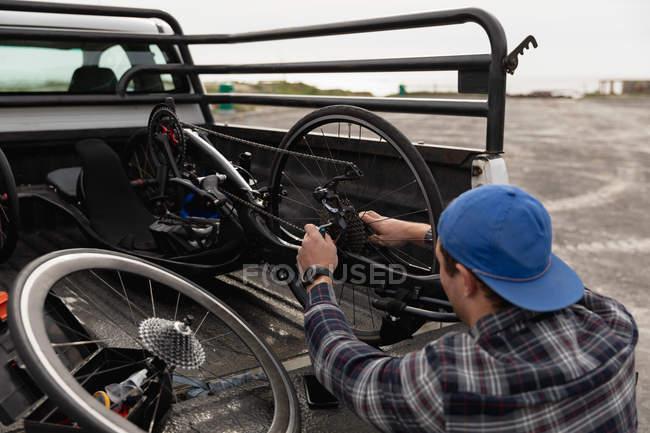 Заднього огляду крупним планом молодого Кавказького чоловіка в інвалідному візку збірка лежачий велосипед в автостоянці біля моря — стокове фото
