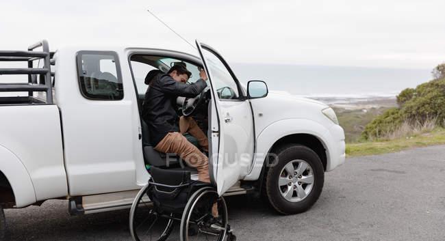 Вид збоку молодого Кавказького чоловіка вихід з інвалідного крісла і в свій автомобіль на автостоянці біля моря — стокове фото