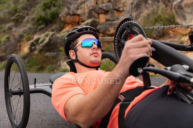 Вид збоку крупним планом молодого Кавказького чоловіка в спортивному одязі на лежачому велосипеді велоспорту на заміському шляху — стокове фото