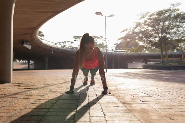 Перед видом молодой кавказской женщины, одетой в спортивную одежду, делая отжимания во время тренировки в солнечный день в парке — стоковое фото