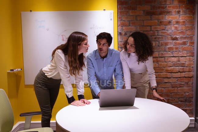 Фронт-вью крупным планом молодой смешанной расы женщина и молодая кавказская женщина и мужчина, стоящие в дискуссии вокруг ноутбука компьютер, работающий вместе в офисе творческого бизнеса — стоковое фото