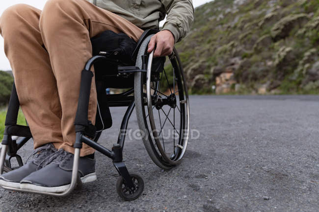 Low section close up of man in a wheelchair enjoying a day out on a road in the countryside — Stock Photo