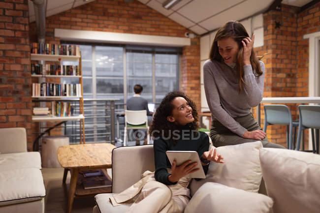 Vista frontal close-up de uma jovem mulher de raça mista sentada em um sofá segurando um computador tablet e conversando com uma jovem mulher caucasiana na sala de estar de um escritório criativo, um colega sentado trabalhando em uma mesa no fundo — Fotografia de Stock