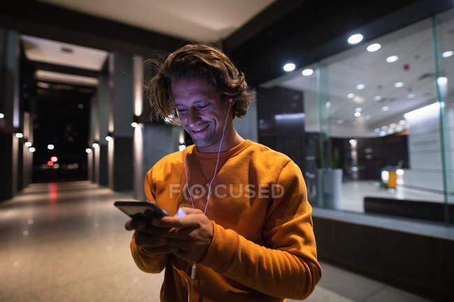 Vista lateral de cerca de un joven caucásico sonriente de pie en la calle por la noche con un escaparate detrás de él mirando un teléfono inteligente y usando auriculares - foto de stock