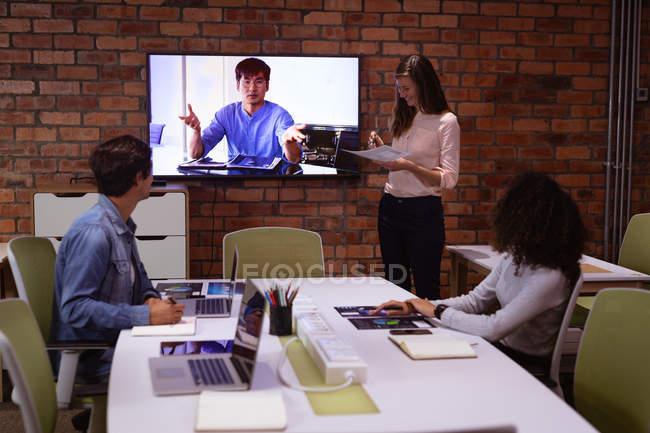 Вид сбоку молодой женщины смешанной расы и молодой кавказки и мужчины, работающего в офисе творческого бизнеса . — стоковое фото