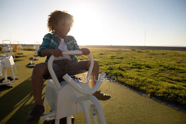 Вид спереди на мальчика смешанной расы на детской площадке у моря, сидящего на скакалке в солнечный день — стоковое фото