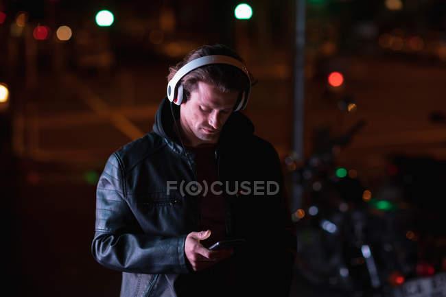 Vista frontal de un joven caucásico de pie en una calle por la noche escuchando música con auriculares, sosteniendo un teléfono inteligente - foto de stock