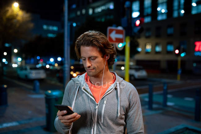 Front view close up of a young Caucasian man using a smartphone with earphones on in the street during his late evening workout — Stock Photo