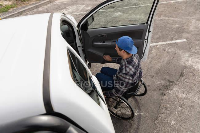 Вид збоку молодого Кавказького чоловіка в інвалідному візку біля відкритих дверей його пікап, припаркованого в автостоянці — стокове фото