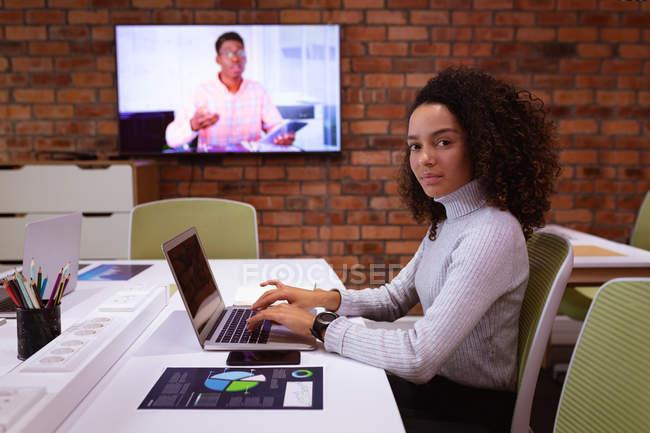 Вид сбоку на молодую расистку, работающую за ноутбуком в офисе креативного бизнеса, поворачивающуюся и смотрящую в камеру. Коллега-мужчина виден на настенном экране, общаясь по видеосвязи — стоковое фото