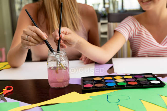 Front view close up of woman doing crafts with her tween daughter in their sitting room — Stock Photo