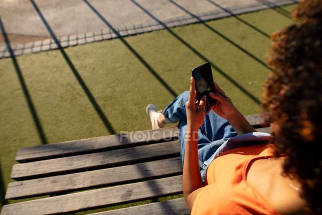 Через плечо вид молодой смешанной расы женщина сидит на скамейке и с помощью смартфона в солнечный день — стоковое фото