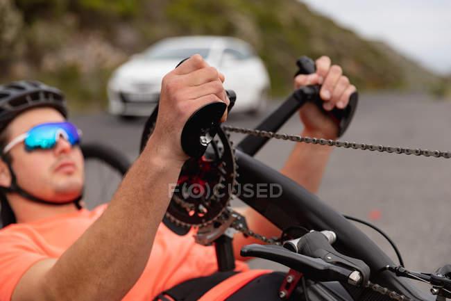 Вид збоку крупним планом молодого Кавказького чоловіка в спортивному одязі на лежачому велосипеді велоспорту на заміському шляху, з автомобілем у фоновому режимі — стокове фото